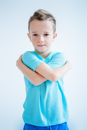 A portrait of a handsome child boy posing in the studio over the blue background. Kids, fashion, casual style, beauty. Фото со стока