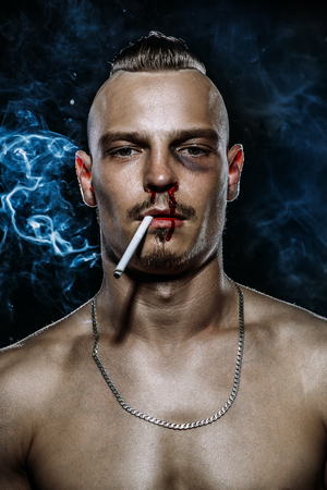 Retrato de un hombre guapo brutal con torso, que fuma un cigarrillo. Belleza masculina, salud. Rockero, punk.