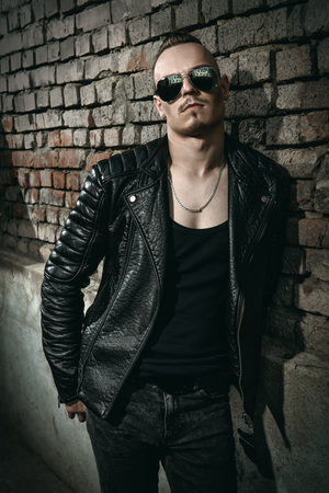 Portrait of a punk man  against a brick wall on the street. Fashion, subculture.