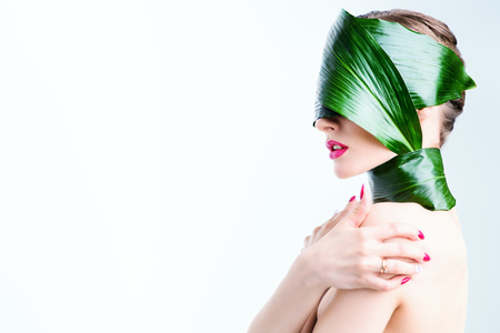 A close up portrait of a beautiful girl with a head rolled up in a leave posing in the studio over the white background. Beauty, nature, make up.