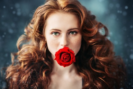 A close up portrait of a lovely mysterious girl with a red rose. Beauty, cosmetics. Stock Photo - 127280523