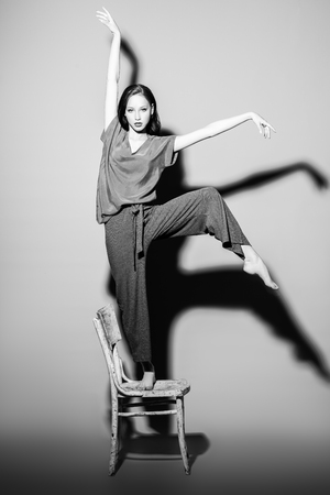 A full length monochrome portrait of a beautiful young woman dancing on the chair over the grey background in the studio. Casual fashion, fitness, yoga. Фото со стока