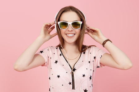 A portrait of a bright girl in the studio over the pink background. Summer casual fashion, optics, beauty.