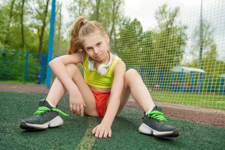Un retrato de cuerpo entero de una chica adolescente deportiva posando en el campo de deportes. Moda deportiva, estilo de vida activo.