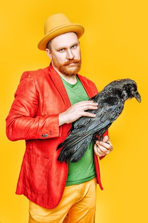 A portrait of a bright man posing in the studio over the yellow background with a black raven. Men, beauty, colors, fashion.