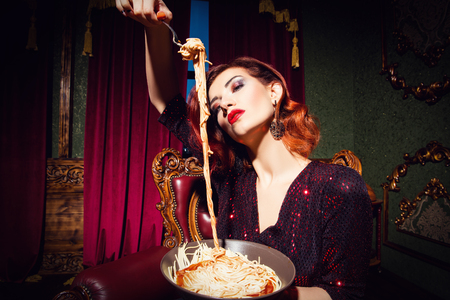 A portrait of a beautiful woman posing in the vintage interior and having a meal. Beauty, fashion, interior.
