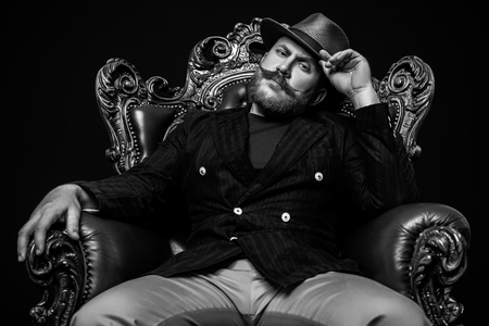 A monochrome portrait of a stylish modern man posing in the armchair. Men fashion, style.