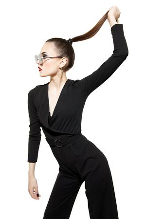 Ein Porträt einer modischen jungen Dame, die im Studio über dem weißen Hintergrund aufwirft. Stil, Schönheit, Mode.