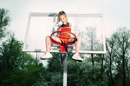 Ein Porträt in voller Länge eines Teenager-Mädchens, das mit einem Mundstück im Freien posiert. Sportmode, aktiver Lebensstil, Basketball.