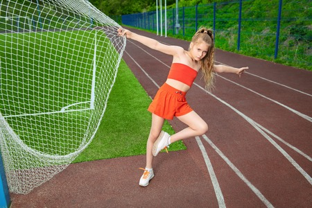 A portrait of a sporty teenager girl posing on the sports ground. Sport fashion, active lifestyle. Archivio Fotografico