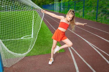 Un retrato de una chica adolescente deportiva posando en el campo de deportes. Moda deportiva, estilo de vida activo.
