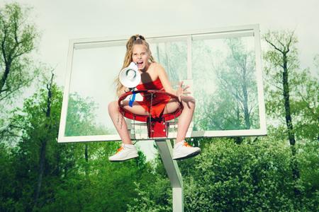 Un retrato de cuerpo entero de una chica adolescente posando al aire libre con una boquilla. Moda deportiva, estilo de vida activo, baloncesto.