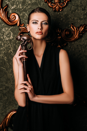 A portrait of a beautiful young dark-haired woman posing in the room. Beauty, cosmetics, fashion, interior.