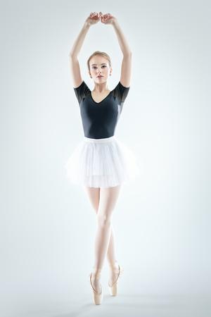 A full length portrait of an elegant refined ballet female dancer posing in the studio over the white background. Talent, fashion for ballet dancers.