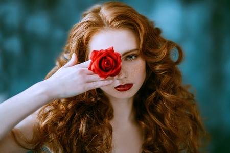 A close up portrait of a lovely mysterious girl with a red rose. Beauty, cosmetics. Stock Photo - 127920404