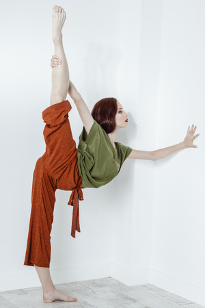 A full length portrait of a young flexible woman over the white background in the studio. Casual fashion, fitness, strethcing.