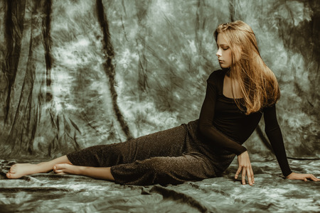 Portret pełnej długości zamyślona młoda kobieta pozowanie kryty. Piękno, moda.