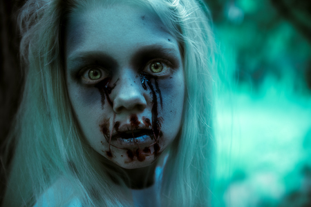 A close up portrait of a scary pale girl from horror film. Zombie, halloween. 免版税图像