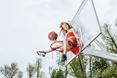A full length portrait of a sporty teenager girl posing on the basketball pinch. Sport fashion, active lifestyle, basketball.