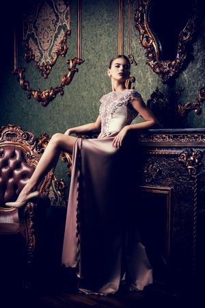 Un ritratto a figura intera di una misteriosa signora in un soffice abito lungo in posa all'interno. Interni, moda.