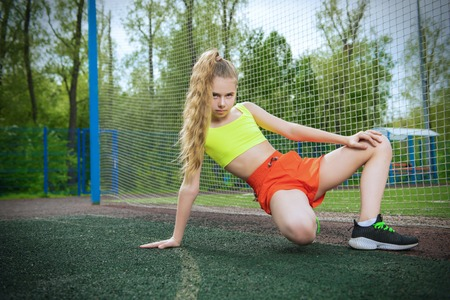 A full length portrait of a teenager girl posing on the sports ground. Sport fashion, active lifestyle.