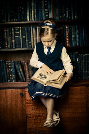 Portrait of a cute little girl sitting by bookshelves in the library. Educational concept. 스톡 콘텐츠
