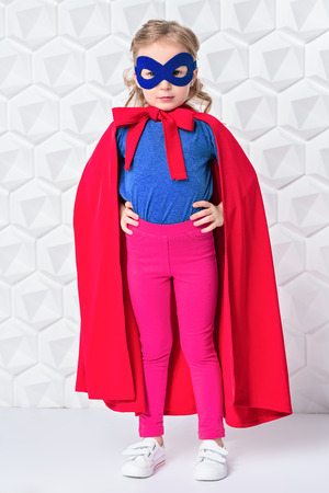 A full length portrait of a funny child girl wearing a costume of a hero and posing in the studio over the white background. Kids, fashion, costume, hero.