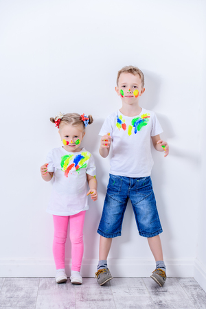 A full length portrait of two happy kids playing with paints. Childhood, leisure activities.