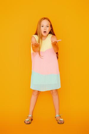Un ritratto a figura intera di una giovane ragazza abbastanza emotiva. Moda casual estiva per bambini. Archivio Fotografico