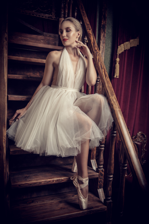 A full length portrait of an elegant refined female ballet dancer posing in the vintage interior on the stairs. Talent, fashion for ballet dancers. Stock Photo