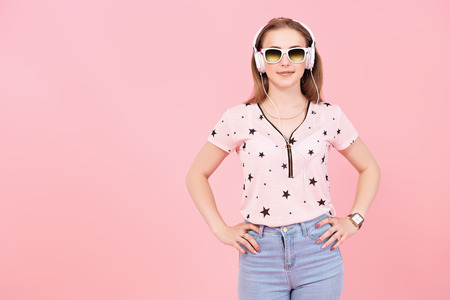 A portrait of a bright beautiful girl in the studio over the yellow background. Summer casual fashion, beauty.