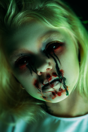 A close up portrait of a scary pale girl from horror film. Zombie, halloween.
