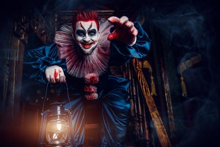 Portret wściekłego szalonego klauna z horroru z latarnią na schodach. Halloween, karnawał.