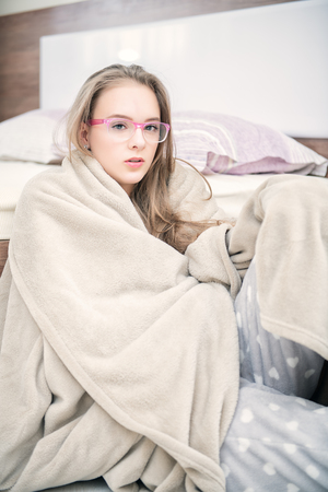 An attractive young girl is sitting wrapped in a blanket on the floor near the bed at home. Beauty, cosmetics.