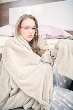 Une jolie jeune fille est assise enveloppée dans une couverture sur le sol près du lit à la maison. Beauté, cosmétiques.