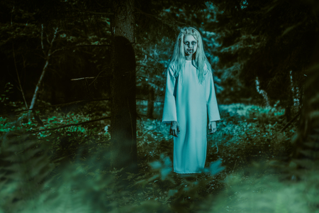 A full length portrait of a scary pale girl from a horror film in the forest. Zombie, halloween. Фото со стока