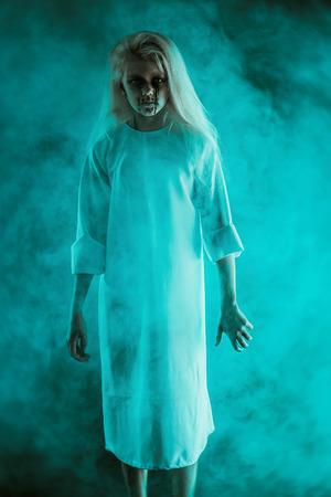 Un retrato de una aterradora niña pálida de la película de terror en la niebla. Zombie, halloween.
