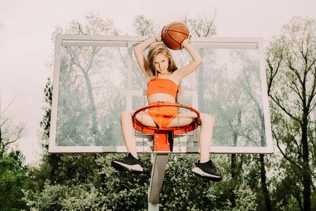 Un retrato de cuerpo entero de una chica adolescente deportiva posando en el pellizco de baloncesto. Moda deportiva, estilo de vida activo, baloncesto.