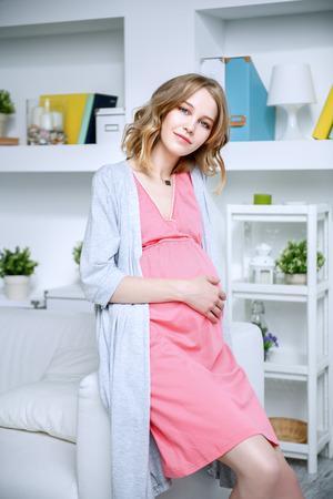 Junge, schwangere Frau im Innenraum. Schwangerschaft und Mutterschaft. Mode für Schwangere. Standard-Bild