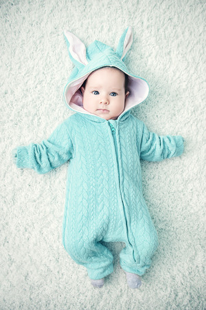 A portrait of a funny baby wearing a jumsuit of a hare. Family, parenthood. Goods for newborns. 写真素材