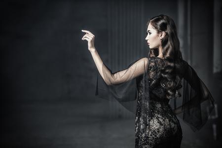 Una bella dama morena con un cuervo en ruinas. Vestido de noche. Belleza de la moda.