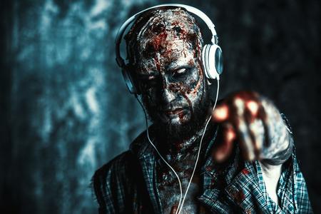 Creepy scary zombie is listening to music with headphones. Halloween. Horror film. Reklamní fotografie
