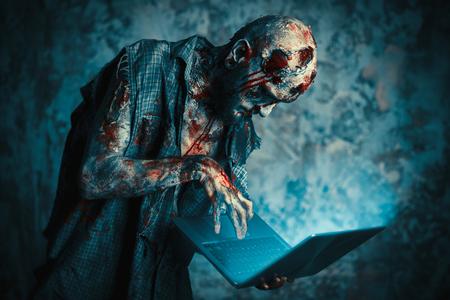 Gruseliger unheimlicher Zombie ist mit einem Laptop. Halloween. Horrorfilm. Standard-Bild