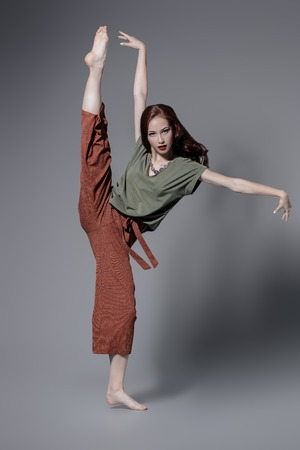 A full length portrait of a beautiful young woman dancing over the grey background in the studio. Casual fashion, fitness, yoga.