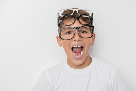A portrait of a cheerful young boy over the white wall. Beauty, summer casual fashion, optics, education. Stock Photo