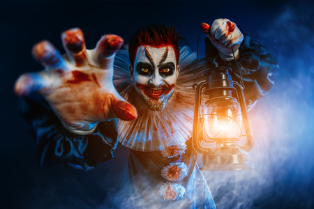 A portrait of an angry crazy clown from a horror film with a lantern. Halloween, carnival. Banco de Imagens