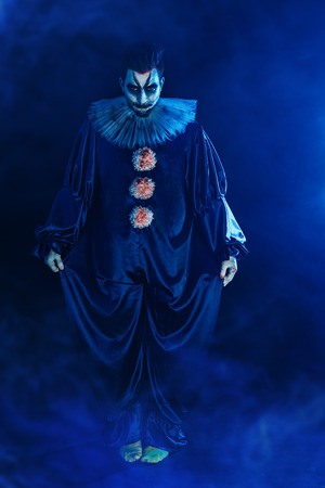A full length portrait of a clown from a horror film. Halloween, carnival.