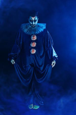 Un retrato de cuerpo entero de un payaso de una película de terror. Halloween, carnaval. Foto de archivo