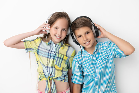 A portrait of two cheerful young kids listening to music in headphones over the white background. Summer casual kids fashion. Stock Photo