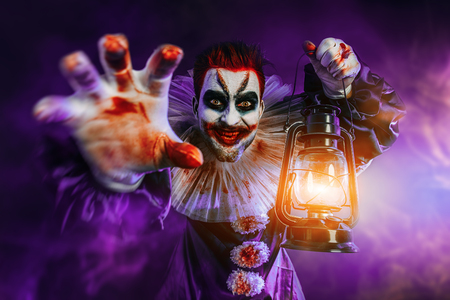 A portrait of an angry crazy clown from a horror film with a lantern. Halloween, carnival. Stock fotó